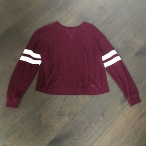 maroon colored sweater with white stripes